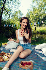 Young Caucasian woman with raspberries on her fingers smiling and posing on a picnic blanket Selective focus