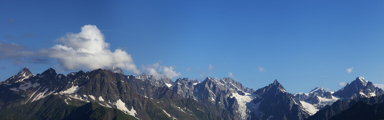 Fototapete - Panorama of high rocky mountains with glacier and sunlit blue sky