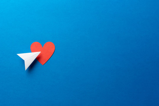 Paper plane with red heart shape on blue background with space for text. Sharing and send concept.