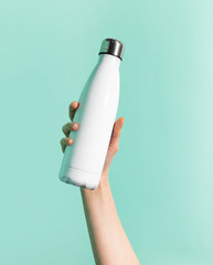 Close-up of female hand holding white reusable steel stainless thermo water bottle isolated on background of cyan, aqua menthe color. Plastic free.