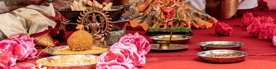 Wedding ceremony, traditional indian hindu marriage ritual with red flowers and attributes