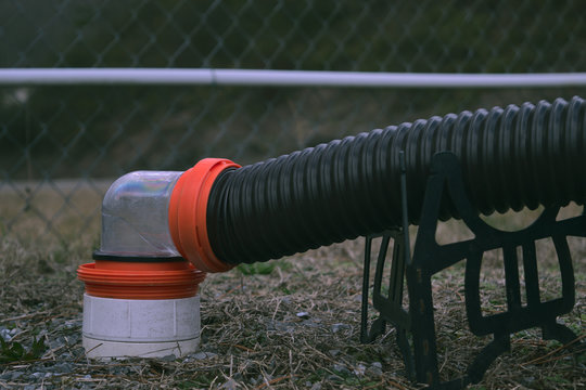 RV sewer hose connected to dump station with 90 degree clear fitting