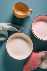 Still life of pastel colored ceramic dishes with ombre linens