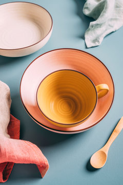 Still life of pastel colored cup, bowl, plate with linens and wooden spoon