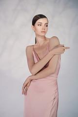 Poster womenART Beautiful woman pose in studio in pink classic dress