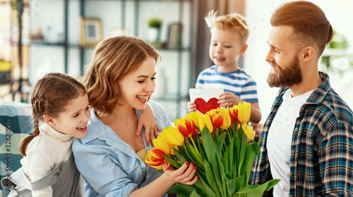 happy mother's day! father and children congratulate mother on holiday  .