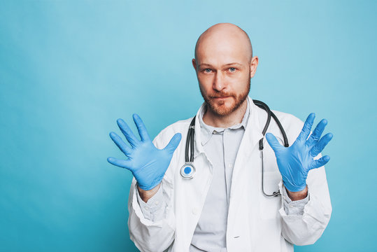 Attractive man bald bearded doctor in rubber medical gloves looking at camera isolated on blue background
