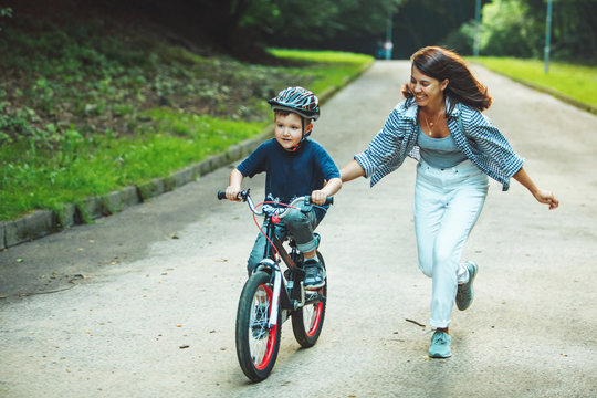mother teaching son how to ride bicycle