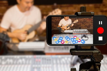 music vlogger streaming a live video while playing acoustic guitar in home studio