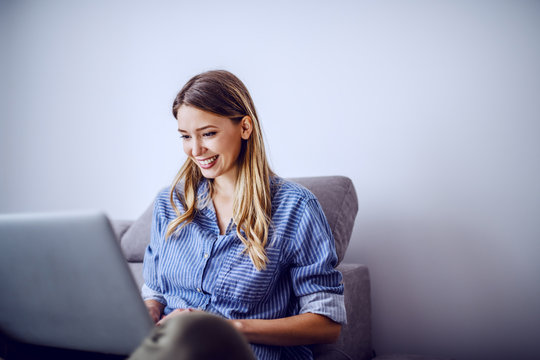 Young attractive smiling caucasian brunette sitting on sofa in living room and using laptop for freelance job.