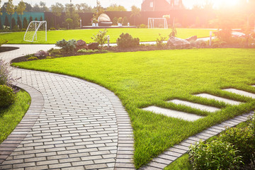 Landscaping of the garden. A tile path between green grass and a lawn with flowers in the sun. Soccer field in the background with copy space.