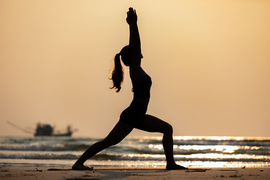 Silhouette Vacation of Asian woman relaxing in yoga Warrior one pose on the sand and beach with sunset beautiful sea in Tropical island,Feeling comfortable and relax in holiday,Vacations Concept