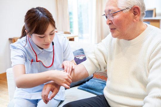 血圧を測る看護師