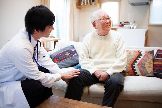 高齢の男性に触診をする医師