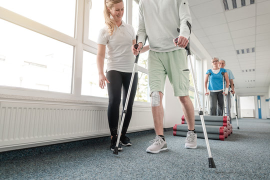 People in rehabilitation learning how to walk with crutches