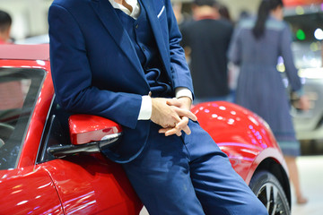 Royalty high quality free stock photo an unidentified man in a suit is leaning against his red car