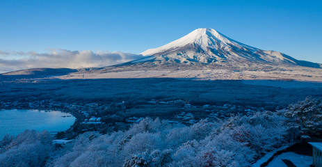 Aerial view of Mount Fuji in winter, iconic snow-capped symbol of Japan, snow covered scenery with freezing fog on trees, lake Yamanaka, clear blue sky - landscape panorama of Japan from above, Asia
