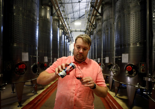Uncanny Wines co-owner Arnold Vlok pours a glass of Merlot, part of a the company's series of canned wines, in Paarl