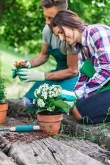 Young loving couple have fun with gardening work on a wooden floor during spring day - Millennial are dressed with green aprons