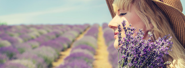 Foto op Plexiglas Lavendel Girl in a flowering field of lavender. Selective focus.