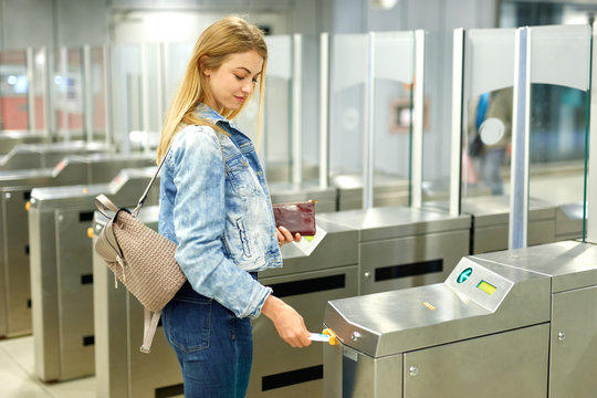 Blonde with long hair passing the turnstiles at subway station