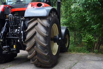a large new red tractor with huge wheels and many mechanisms stands near green trees before starting work