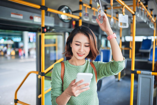 young beautiful asian woman browsing and typing messages in a public bus