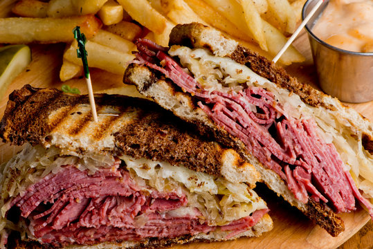 Reuben Sandwich, classic traditional American bar/pub menu item, on grilled rye bread, corned beef, Swiss cheese, sauerkraut and topped with thousand island dressing and french fries in background.