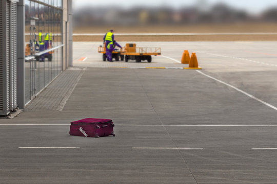 The suitcase lost by the airport staff lies on the floor. Concept of lost luggage.