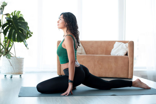 Attractive Latin woman doing yoga in living room. Pigeon pose