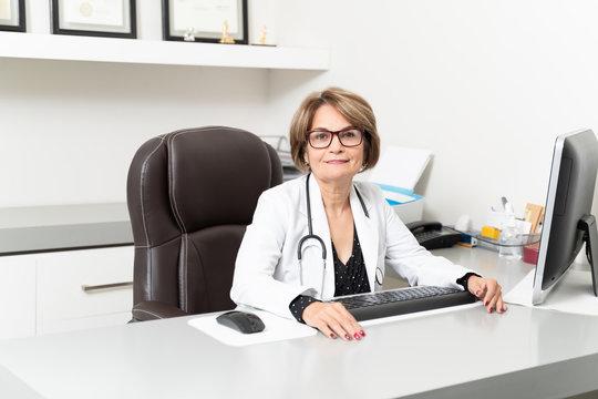 Smiling Elderly Doctor Working In Hospital