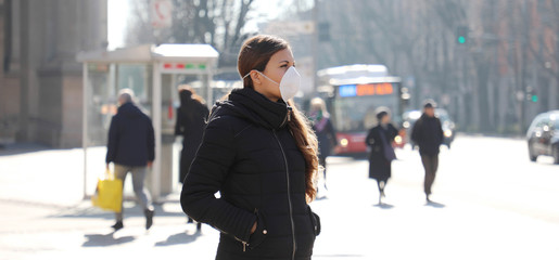 Spoed Fotobehang Milan COVID-19 Young woman in city street wearing face mask protective for spreading of Coronavirus Disease 2019. Panoramic banner view of girl with surgical face mask against SARS-CoV-2.