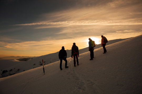 Hikers silhouette at dawn on Mount Ciucas in winter watching the sunset