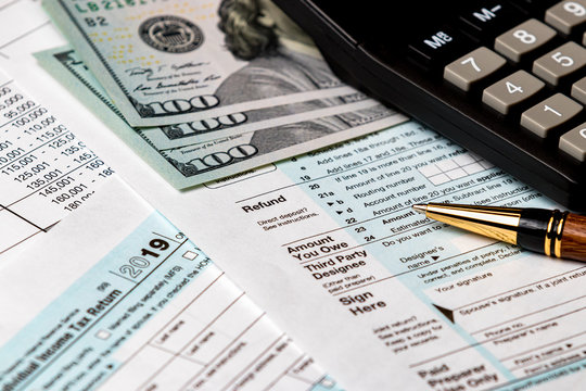 1040 income tax return form 2019 with money, calculator, and pen. Focus on refund. Concept of filing taxes, payment, refund and April 15, 2020 tax deadline