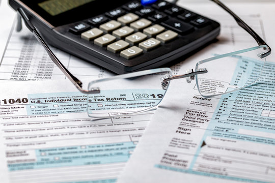 1040 income tax form 2019 with calculator and focus through glasses. Concept of filing taxes, payment, refund, and April 15, 2020 tax deadline