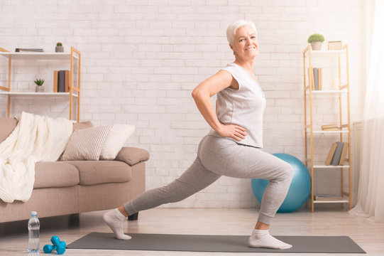 Sporty senior lady doing lunges at home, empty space