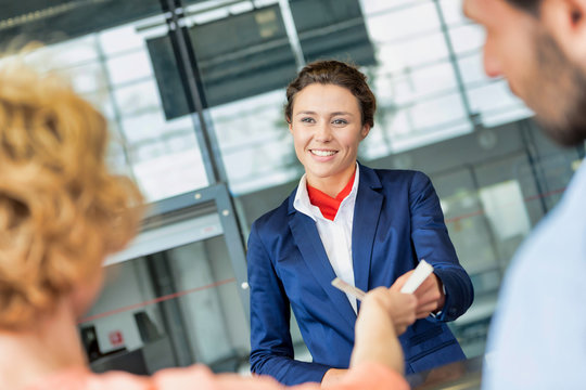 Portrait of young attractive passenger service agent giving boarding with passenger after check in at airport