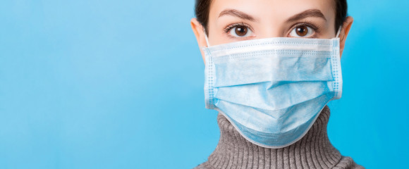 Portrait of young woman wearing medical mask at blue background. Protect your health. Coronavirus concept