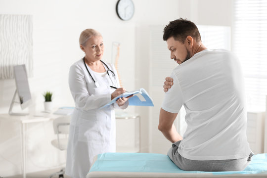 Female orthopedist examining patient with injured arm in clinic