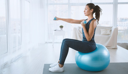 Poster Fitness Young woman with gym ball and dumbbells at home, blank space