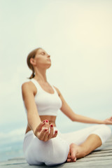 Yoga and meditation. Close up of young woman in lotus pose on wooden deck with sea view.