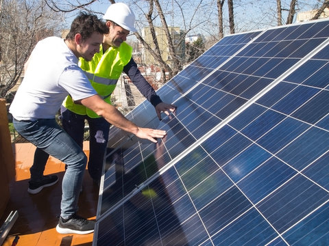 Caucasian seasoned technician showing the solar panels to his young client