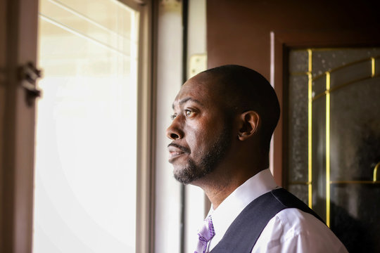 A portrait of an African-American man looking outdoors in a home