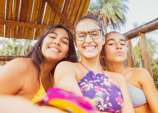 A selfie of three young girl friends, smiling while looking at the camera.