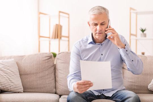 Senior man talking on mobile phone holding document