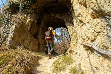 Female hiker walks through a natural mountain tunnel