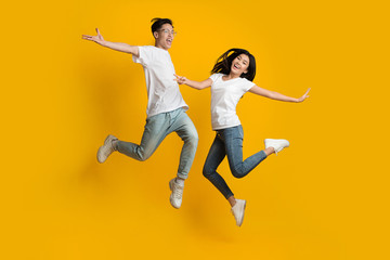 Emotional asian couple jumping over yellow background Fotomurales