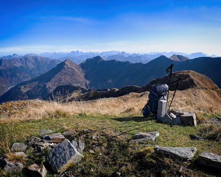 Alpine panorama with backpack and trekking poles. Conceptual image of adventure and freedom. Carnic Alps, Friuli, Italy.