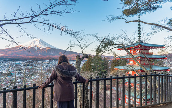 Traveller woman looking on Japanese Fuji mountain on blue sky.