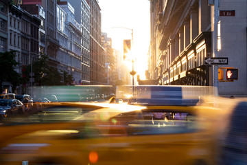 Tuinposter New York TAXI New York City yellow taxi cabs speeding through the intersection of 23rd Street and 5th Avenue with sunlight shining between the background buildings in Midtown Manhattan